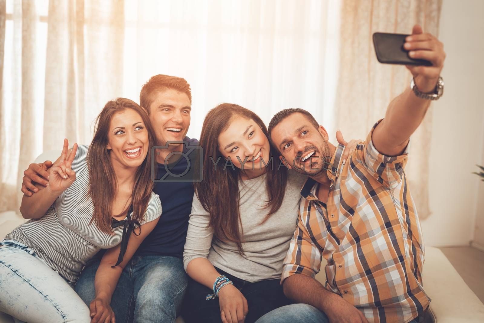 Four cheerful best friends having nice time in an apartment and taking selfie.
