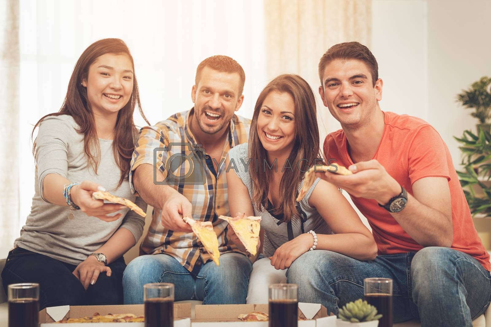 Four cheerful friends hanging out in an apartment. They are eating pizza and looking at camera.