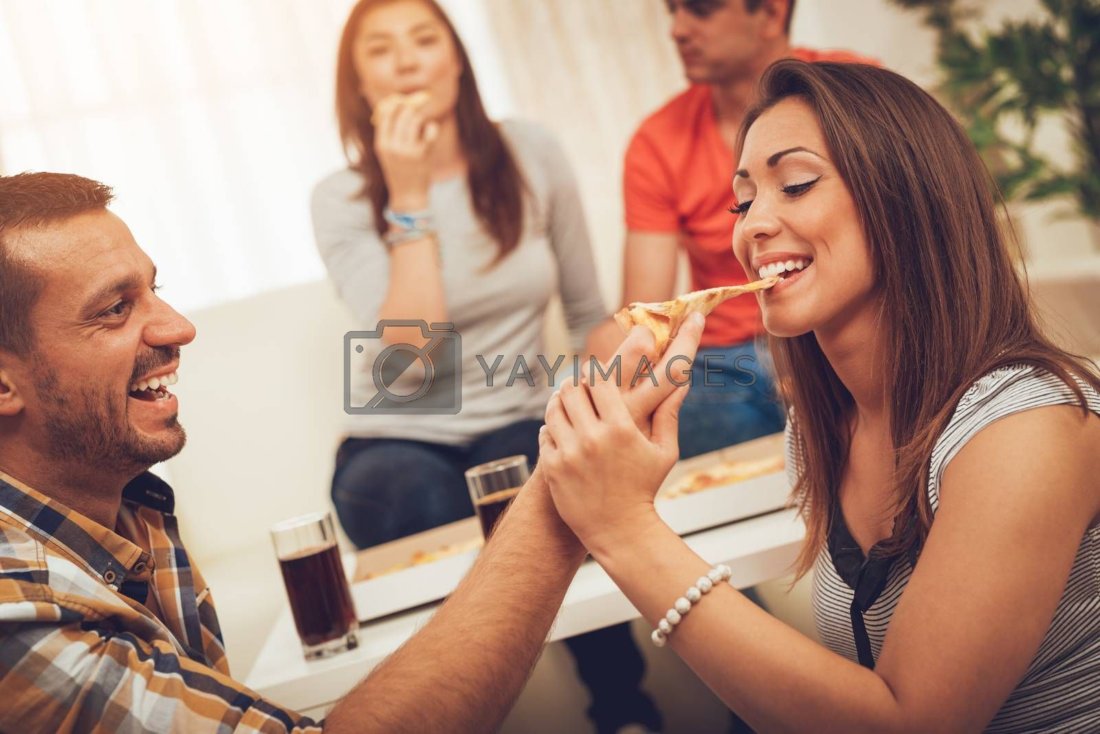 Beautiful young smiling couple sharing pizza and hanging out in an apartment.