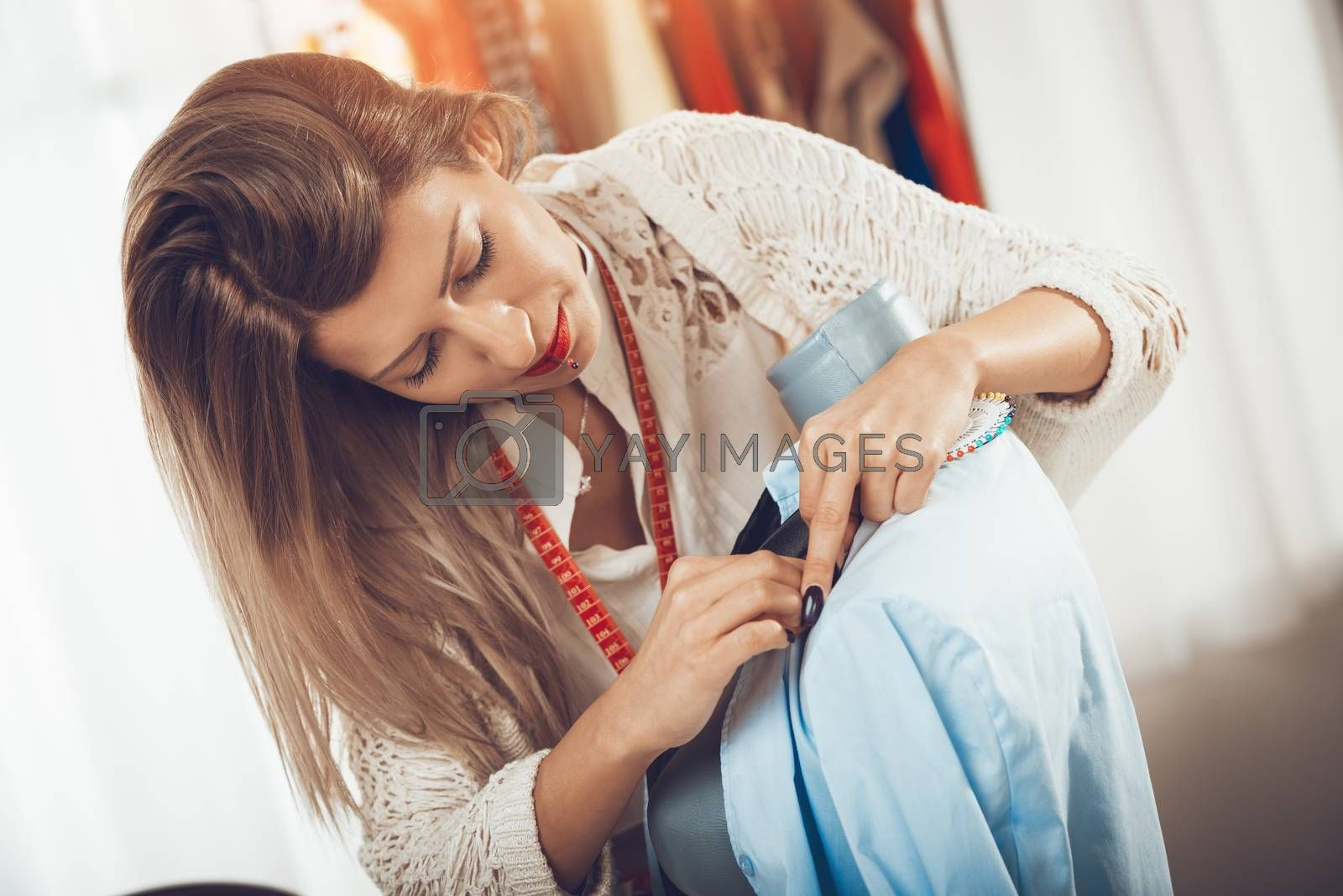 Young beautiful woman with straight pin in her mouth tailor clothes on a mannequin.