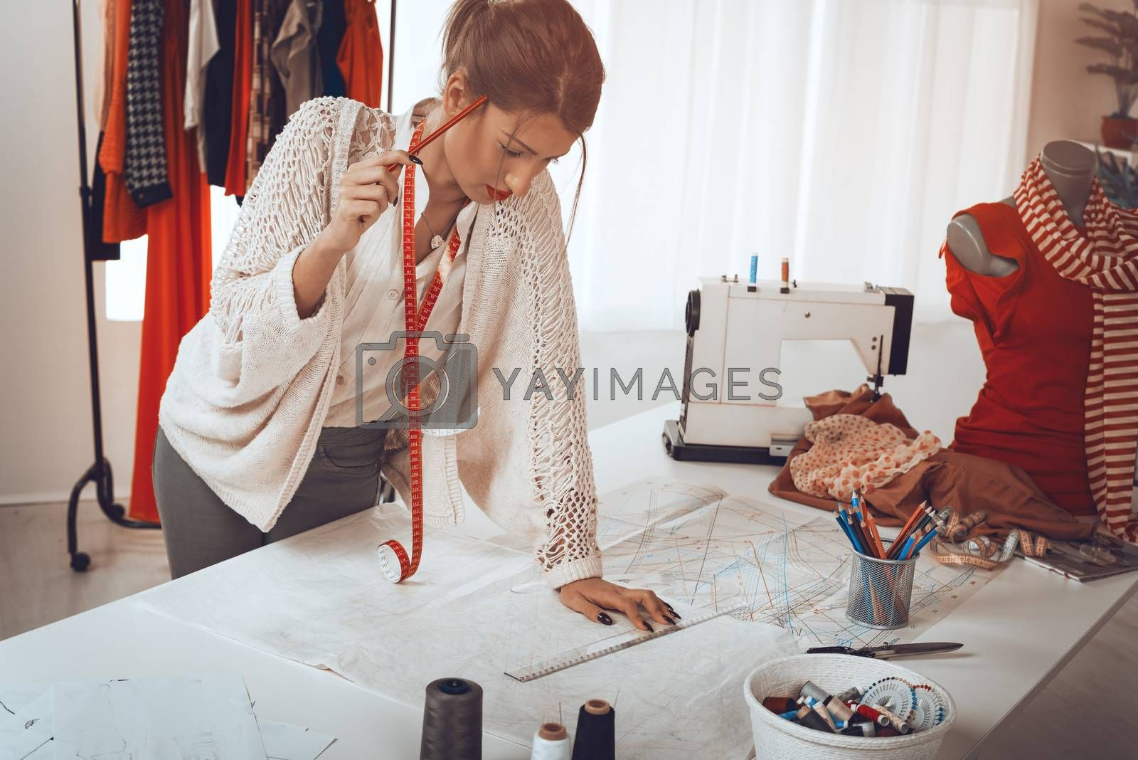 Young pensive female fashion designer with tape measure draped over the neck drawing on sewing pattern with a ruler.