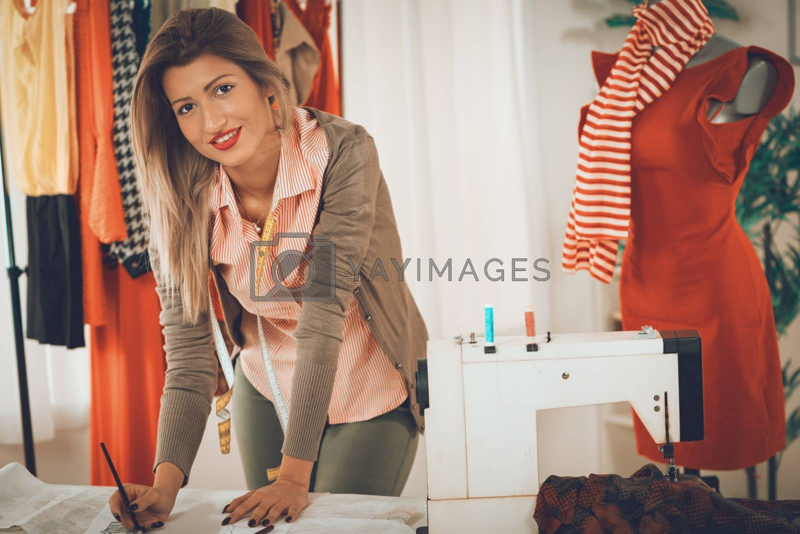 Young smiling woman tailor with tape measure draped over the neck drawing on sewing pattern. Looking at camera.
