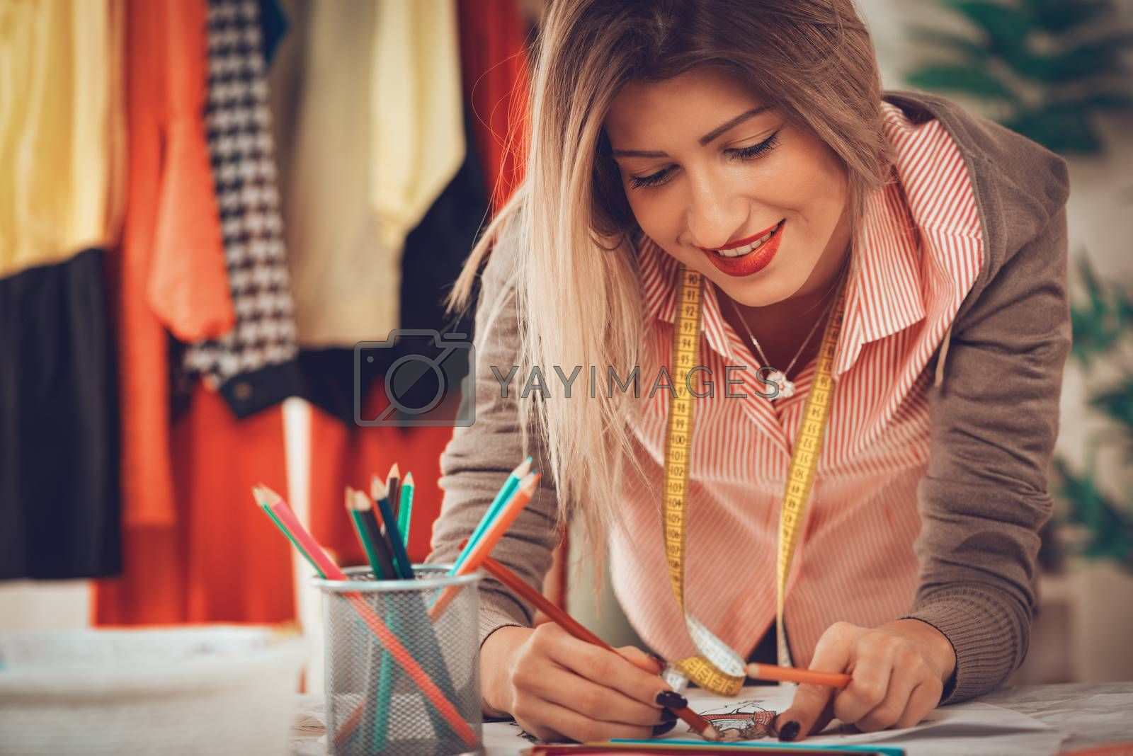 Young female fashion designer with tape measure draped over the neck drawing on sewing pattern.