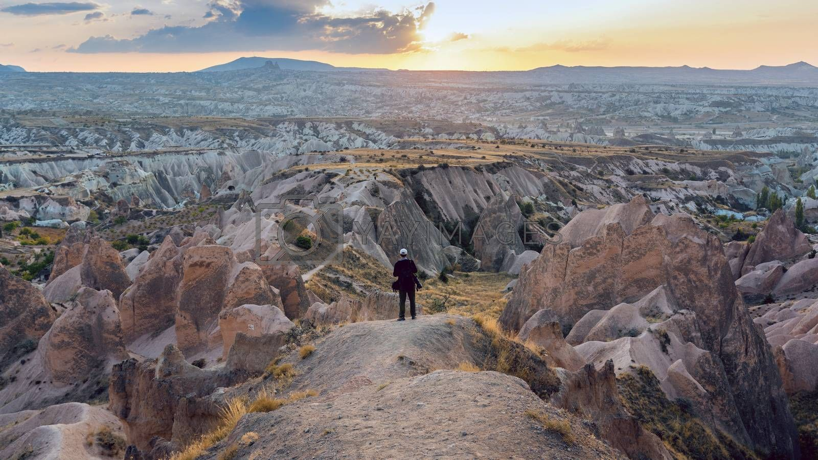 Professional photographer standing on mountain landscape of Cappadocia, Turkey.