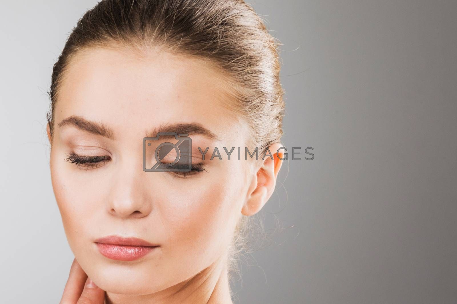 Young beautiful woman face portrait with healthy skin, eyes closed