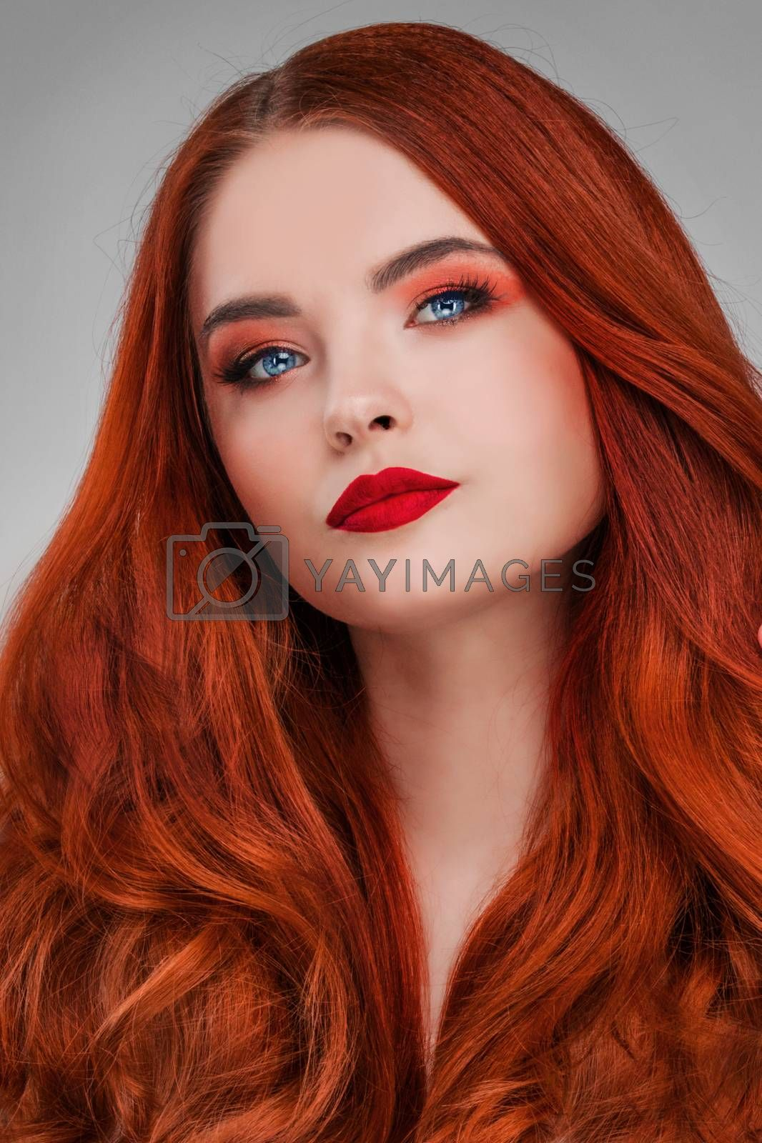 A beauty shot of a young woman with red hair and beauty make-up