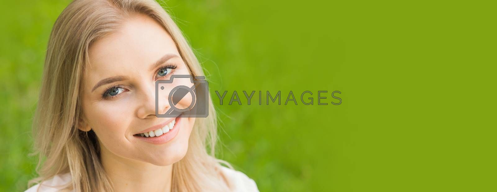 Beautiful woman portrait on spring grass meadow copy space