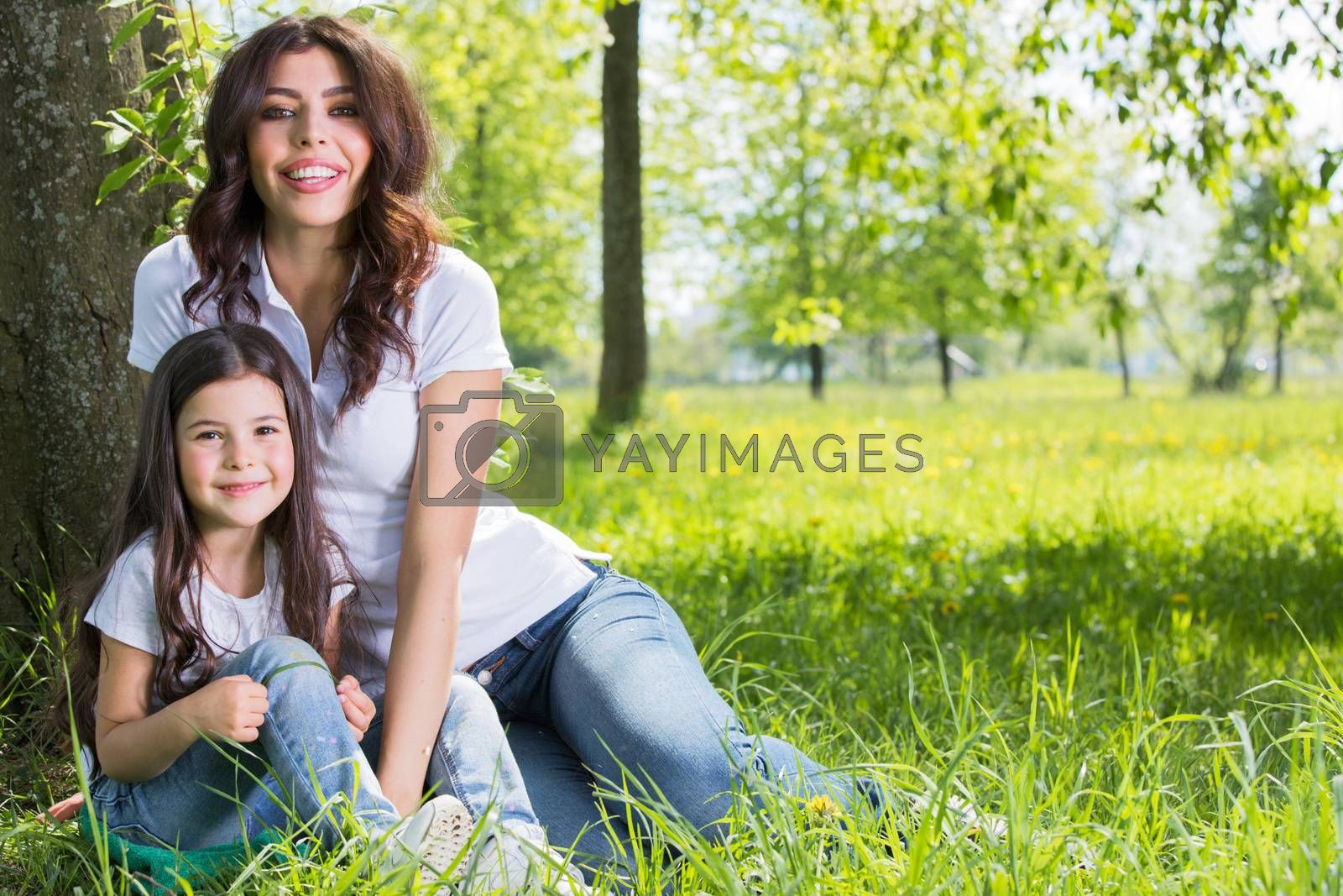 Happy mother with her daughter sitting on grass under the tree in park