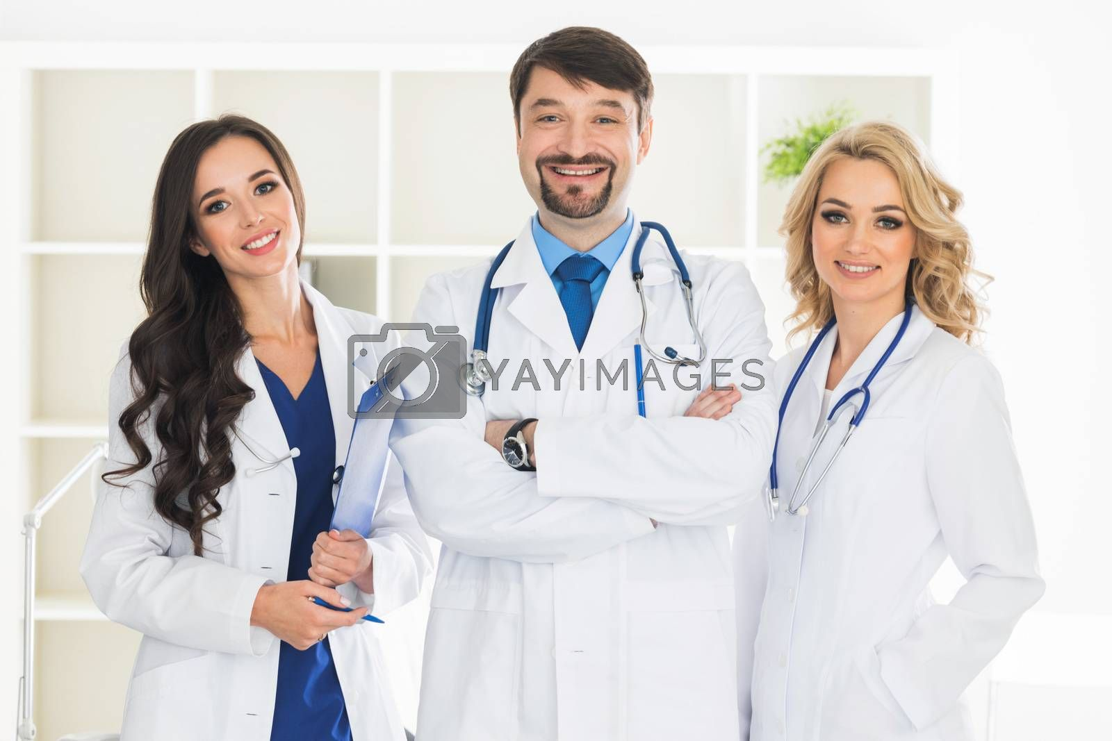 Smiling medical doctors with stethoscopes in medical clinic office