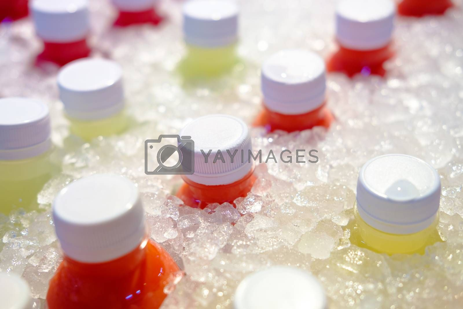 Close-up of Fresh juice of different exotic fruits bottles on the ice box. Mix of plastic bottles on the ice bucket for sale in food market.