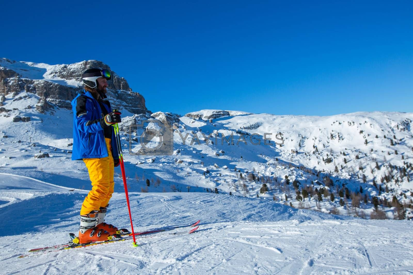 Alpine skier stand on slope in winter mountains Dolomities Italy in beautiful alps Cortina d'Ampezzo Cinque torri mountain peaks famous landscape skiing resort area