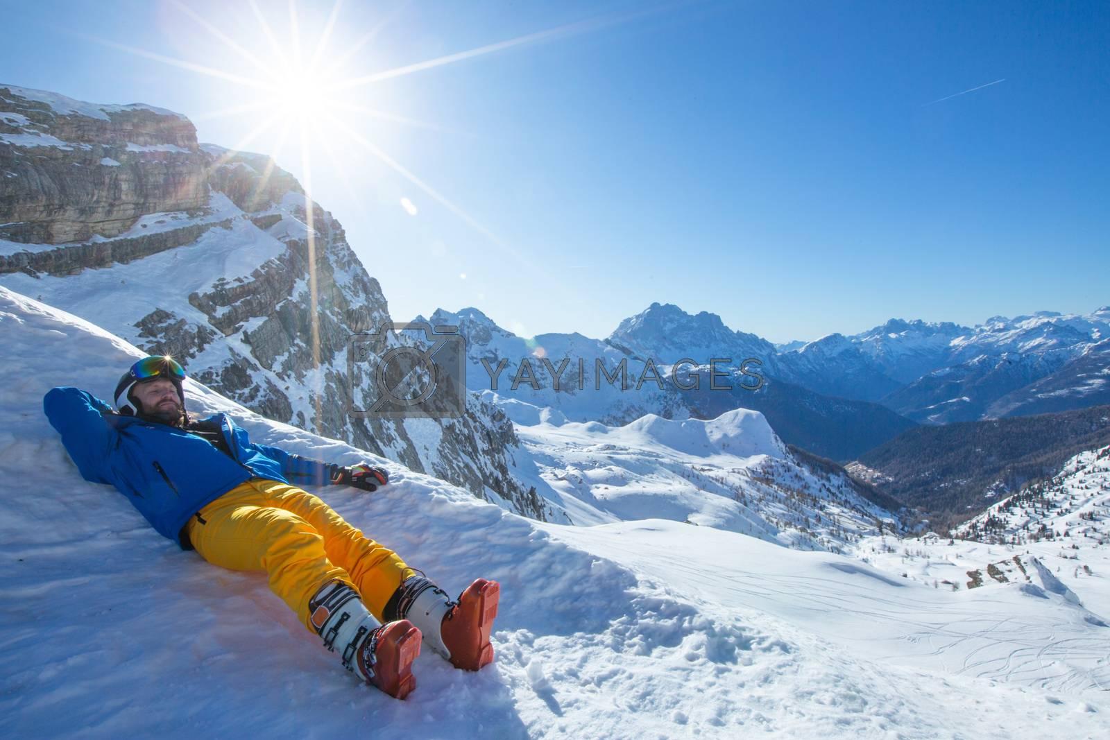 Alpine skier lay in winter mountains Dolomities Italy in beautiful alps Cortina d'Ampezzo Cinque torri mountain peaks famous landscape skiing resort area enjoy sunlight