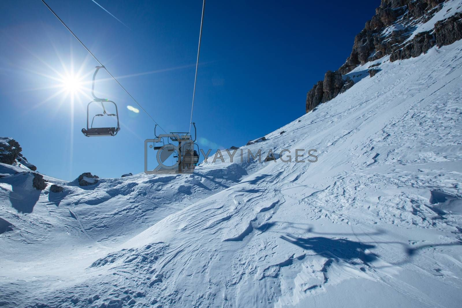 Ski lift chairs on bright winter day Dolomities Dolomiti Italy in wintertime beautiful alps mountains and ski slope Cortina d'Ampezzo Cinque torri mountain peaks famous landscape skiing resort area
