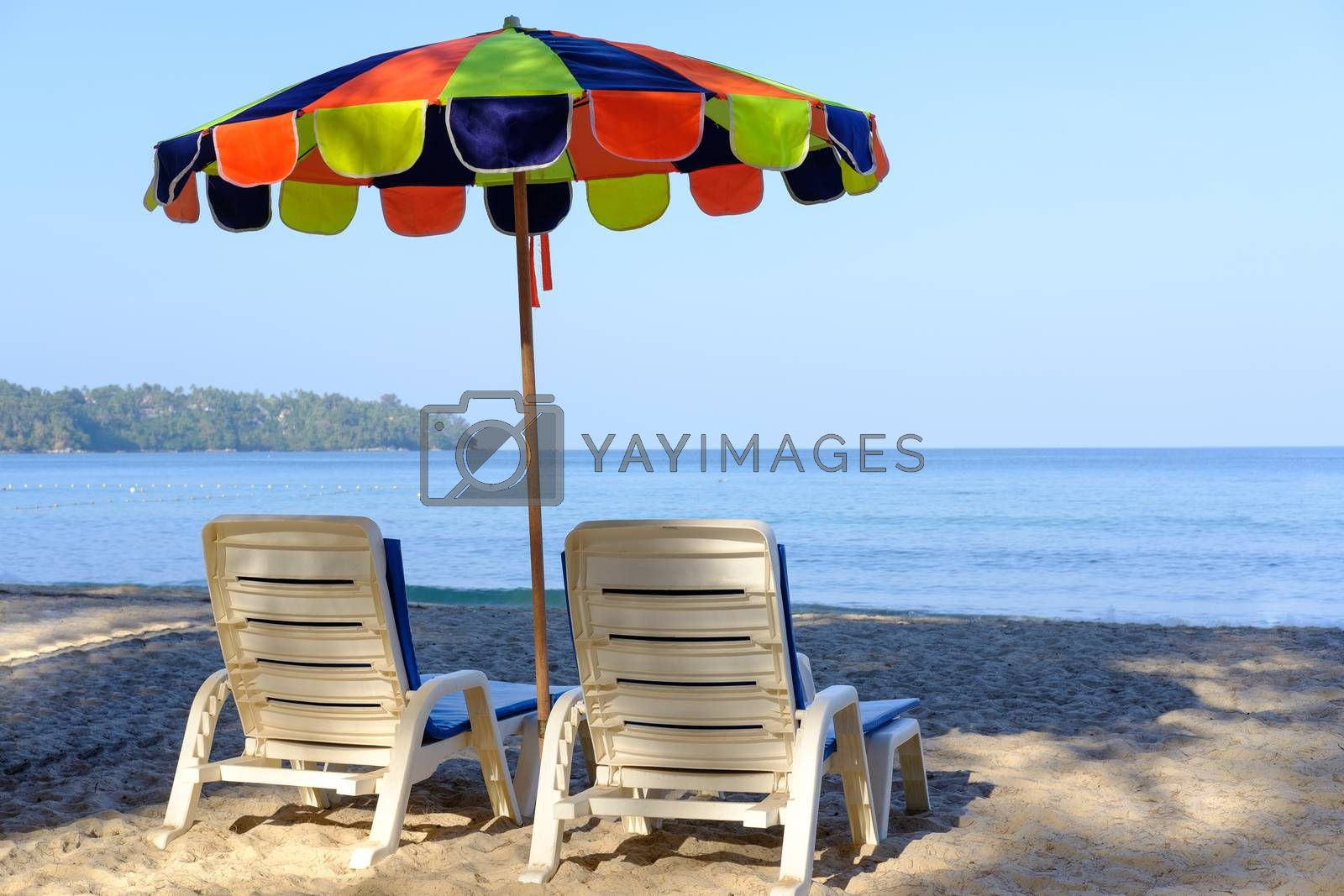 Beach bed and cheerful colorful parasol on tropical beach with blue sky and blue sea. Closeup of Back view beach chairs and umbrella for  summer vacation and holiday concept.