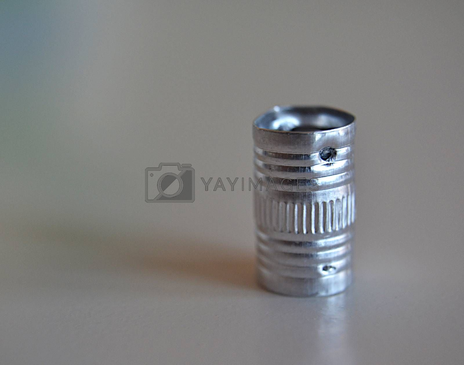 Small metal tube, glossy cylindrical and vertically positioned