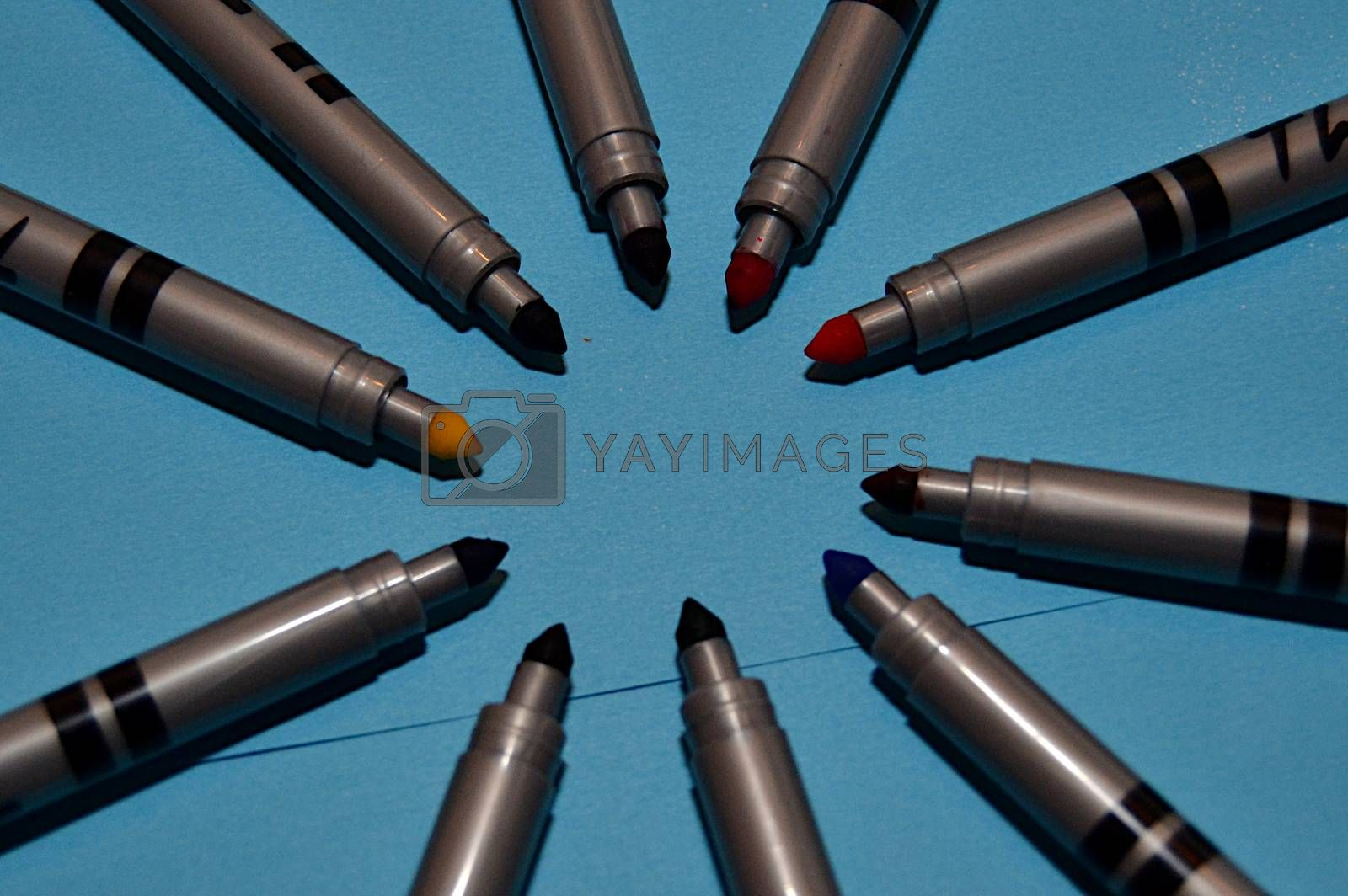 Coloured markers of various colours forming a circle on a blue background