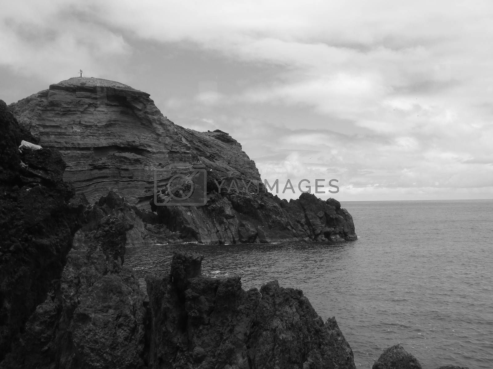 Fantastic views in black and white of the Madeira coast with the blue sea and the volcanic rock