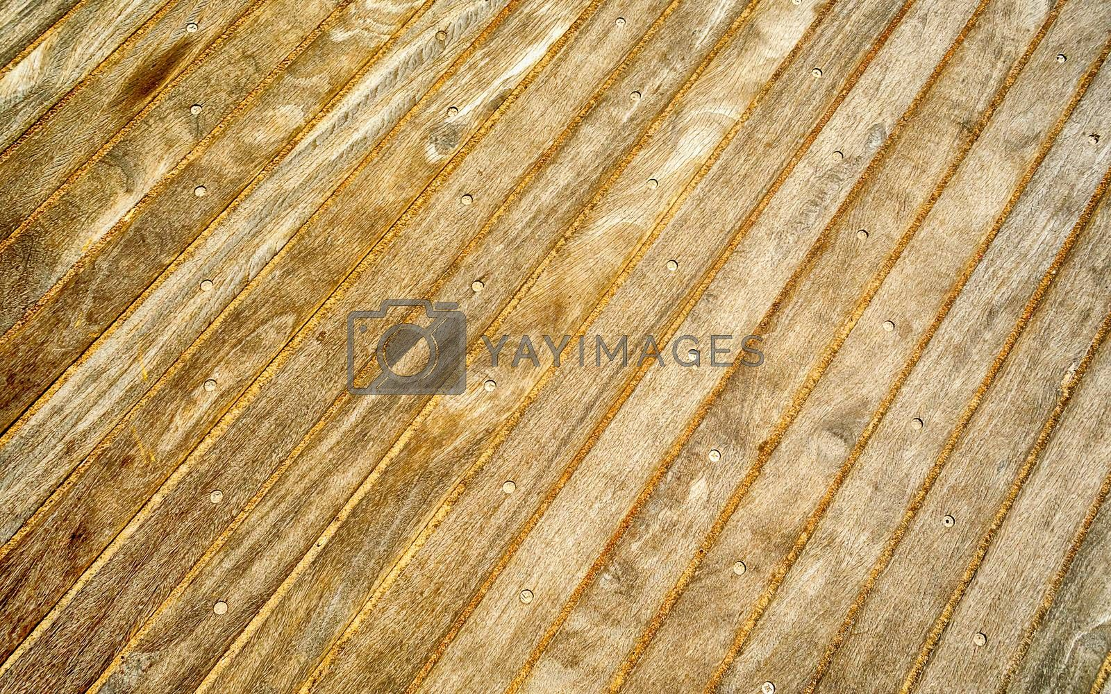 Wooden boardwalk, weathered and rough textured, suitable to be used as background,