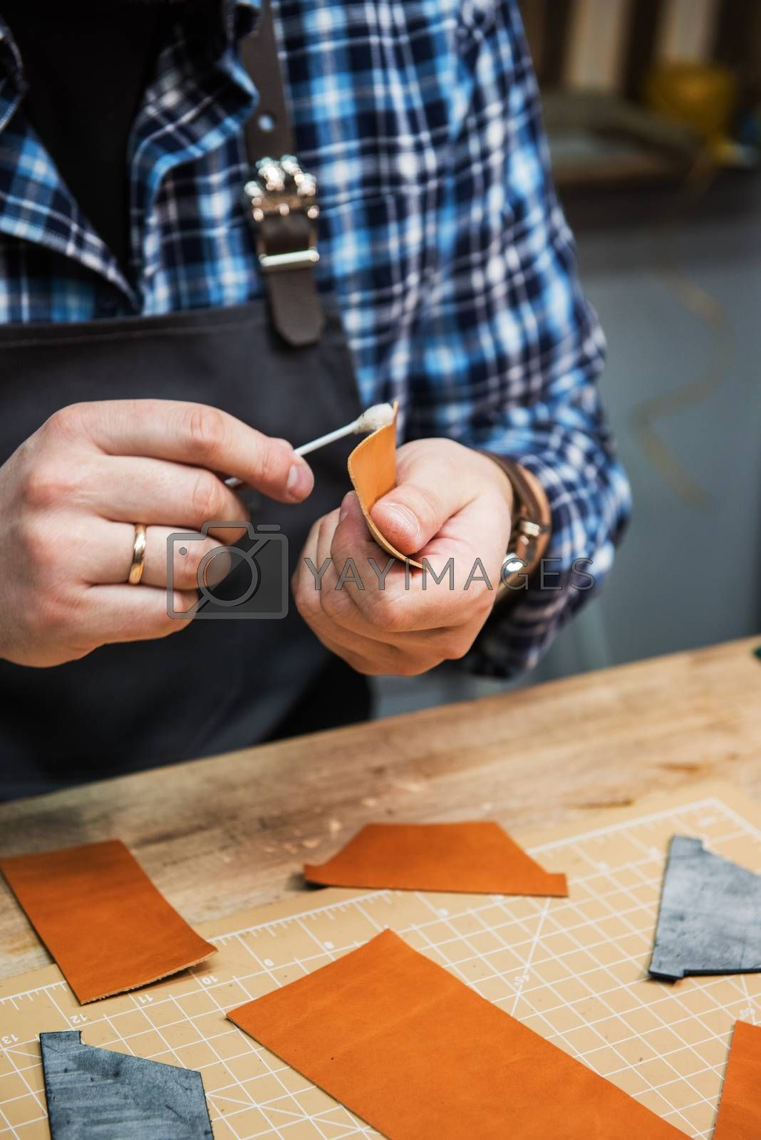 Man making leather wallet at a workshop. Concept of handmade craft production of leather goods.
