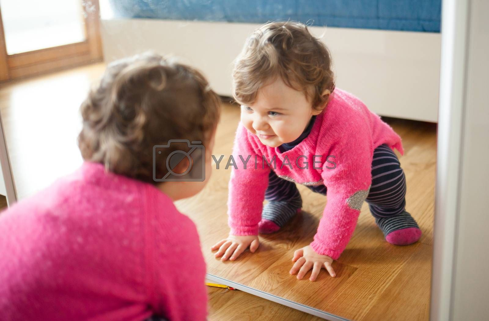 Toddler baby girl playing with mirror in the bedroom by Antonio_Gravante