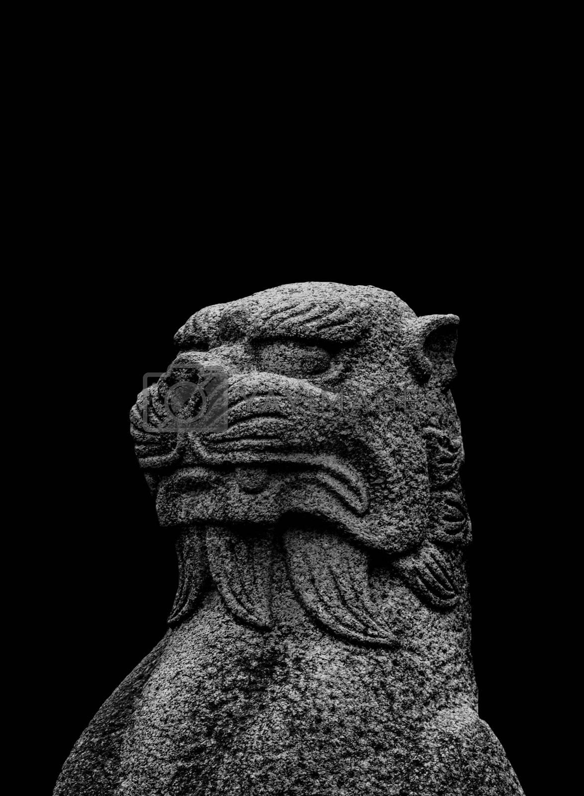 Japanese mythological feline stone sculpture isolated on black background