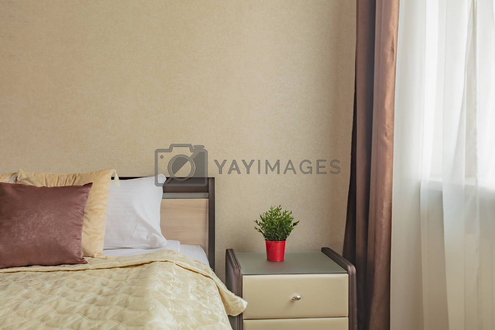 pillow on bed and nightstand in cozy comfortable bedroom in beige color