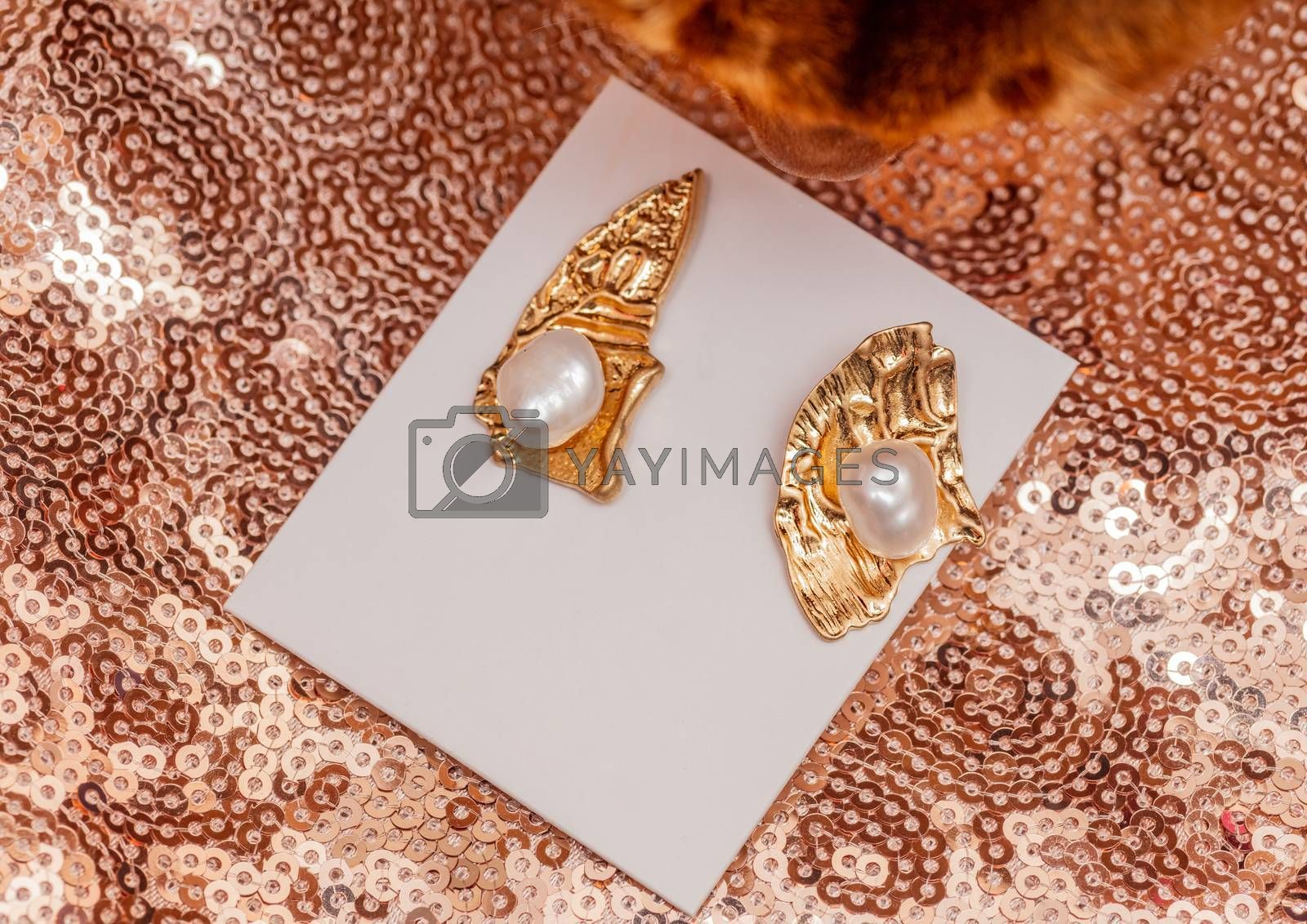 Modern asymmetrical golden earrings with pearl beads on golden shiny background