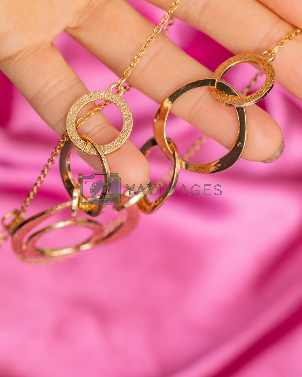 Hand holding Beautiful shiny golden asymmetric necklace with different circle forms over pink background