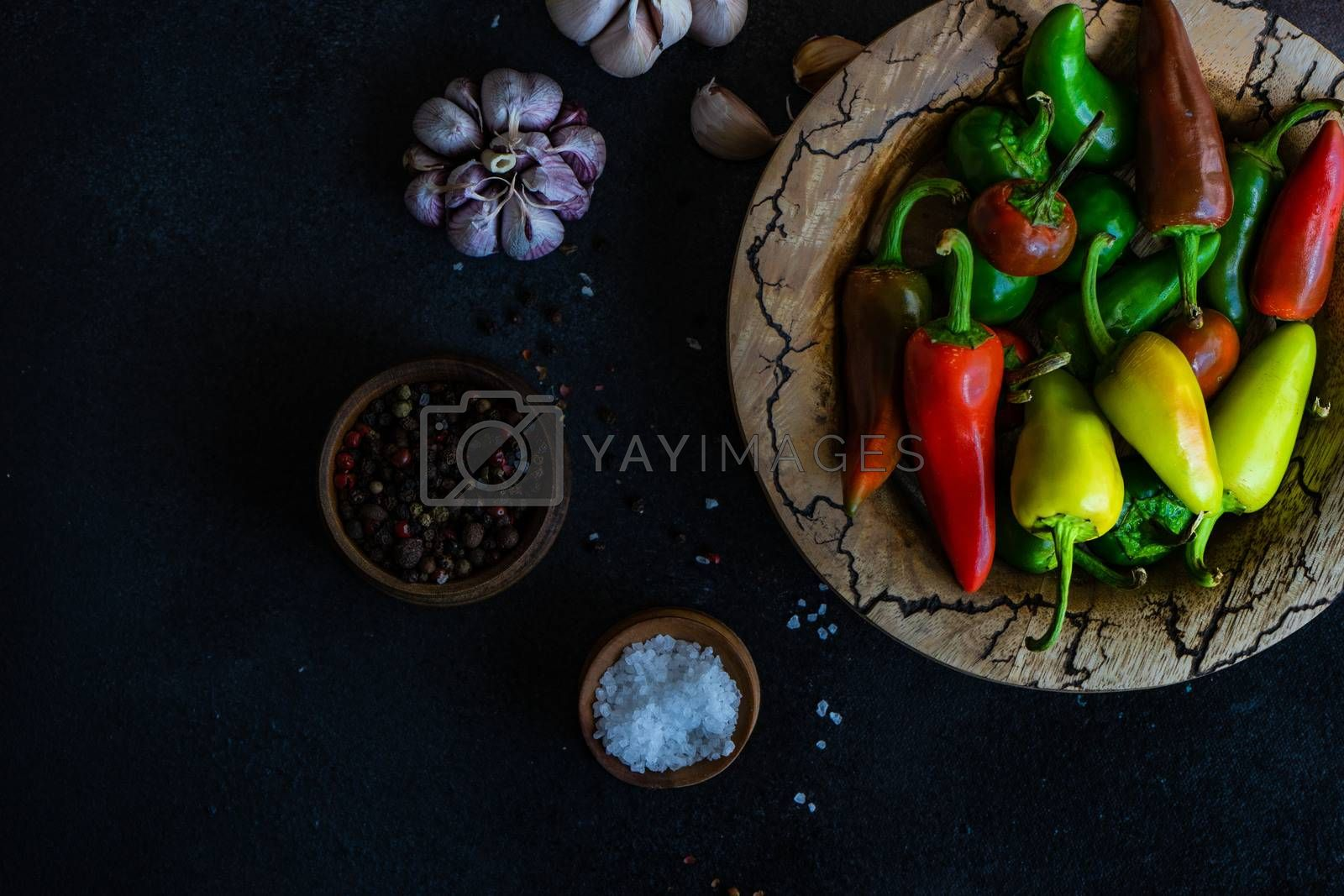 Cooking concept with paprika peppers, pepper spice, garlic heads and sea salt on stone background with copy space