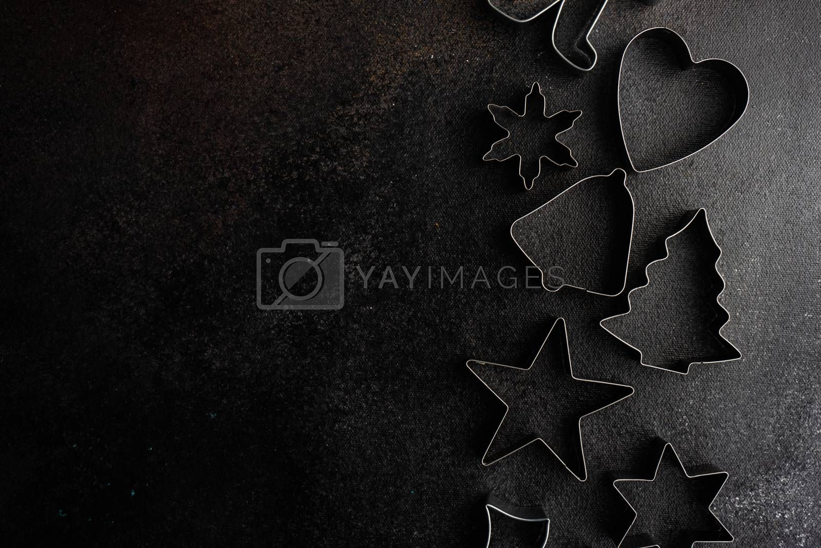 Christmas cooking concept with cookies cutters on stone background with copy space