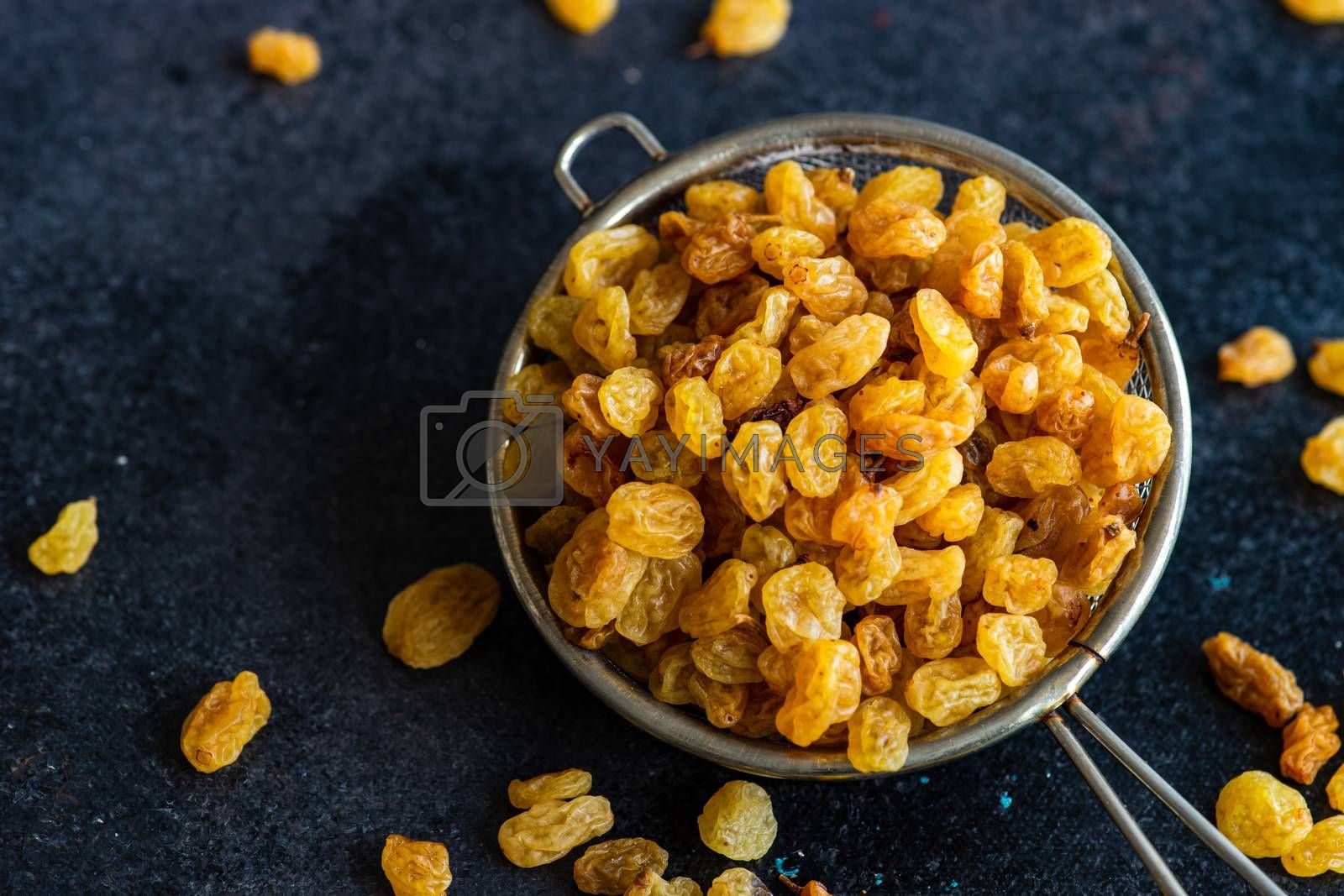 Sweet baking concept with raw raisins on dark stone background with copy space
