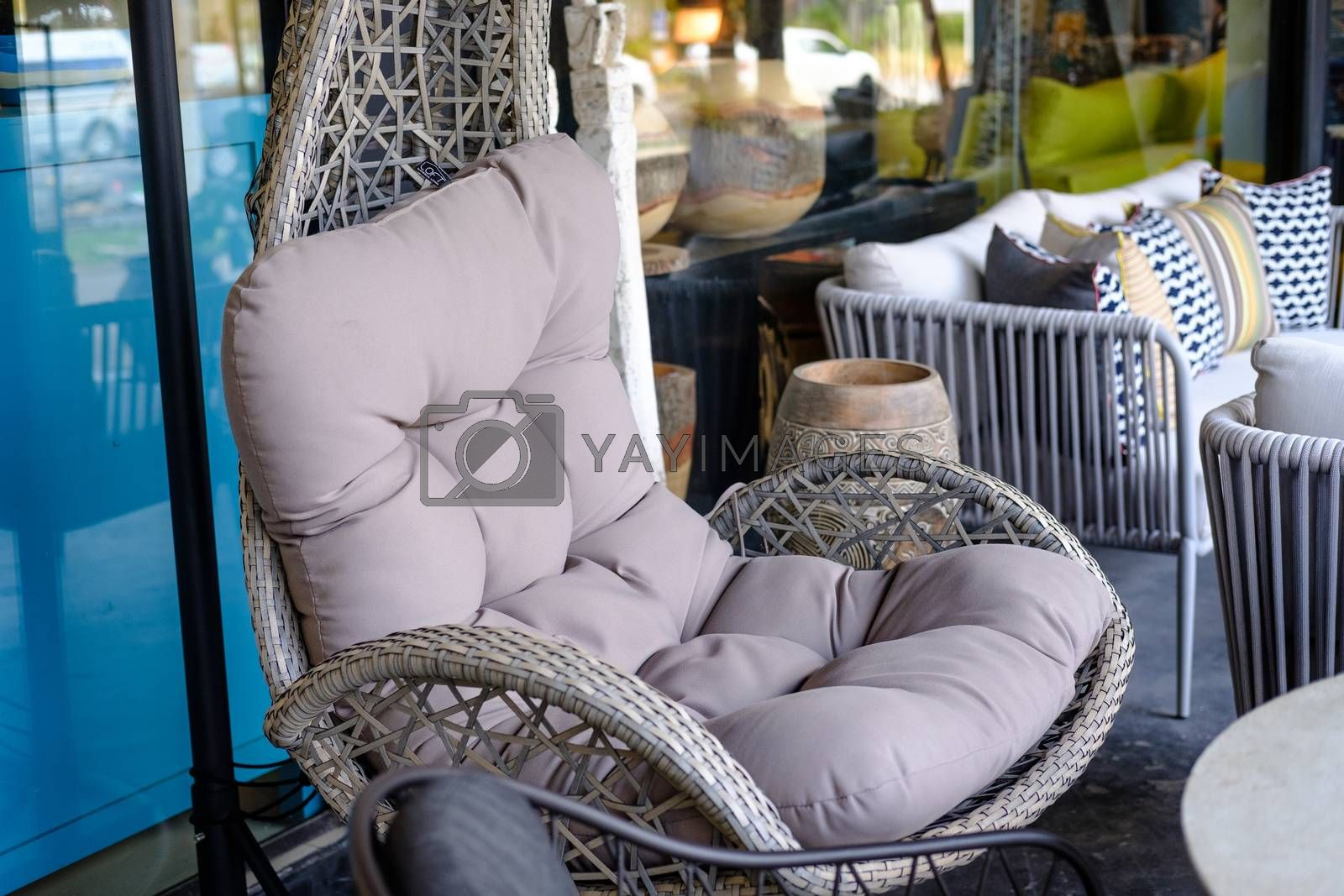 Closeup Empty hanging wicker Comfortable chair with  pillow. Modern design for Terrace, beach or outdoor patio decoration.