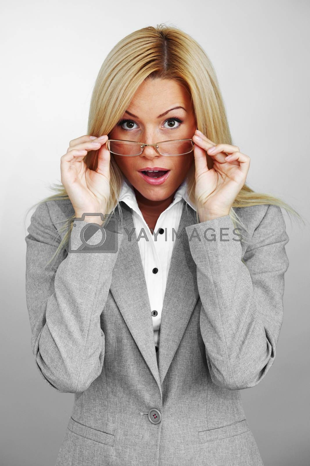 Shocked young business woman wearing gray suit and glasses on grey background