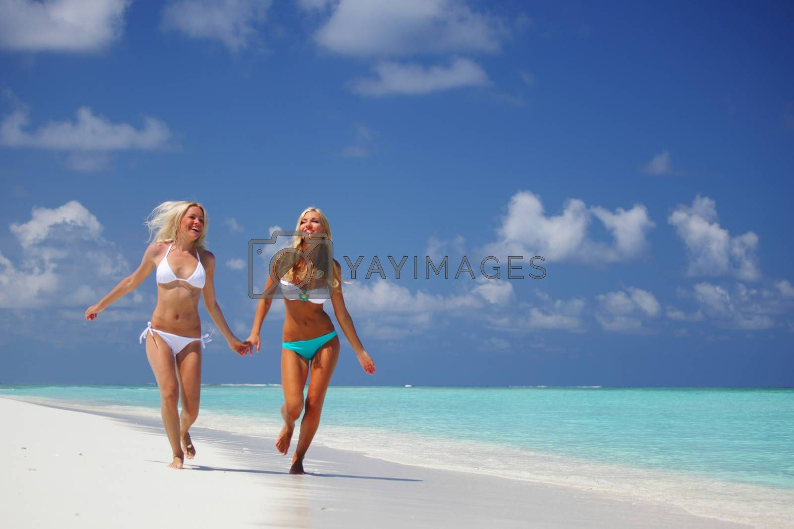 Two happy smiling girls female friends run along ocean coast beach holding hands, vacation at Maldives