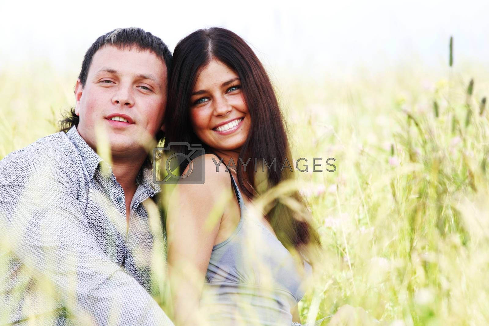 Happy young couple outdoors, two lovers on grass field