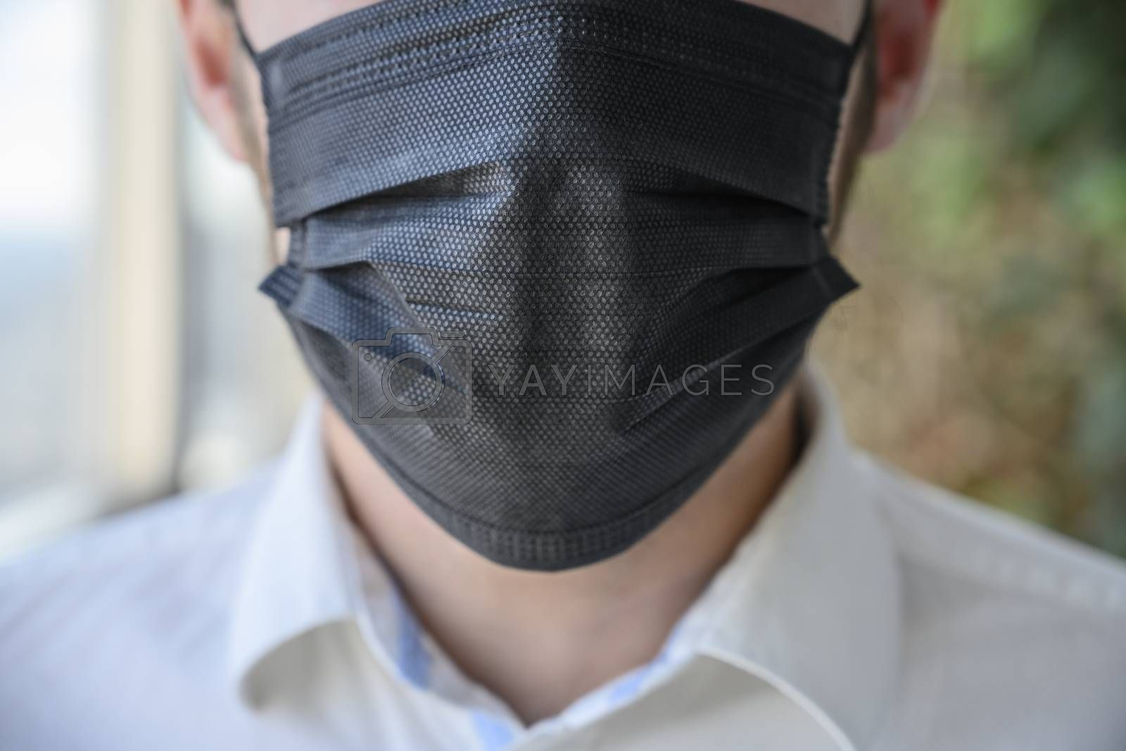 A man wearing a black respiratory mask on his face.