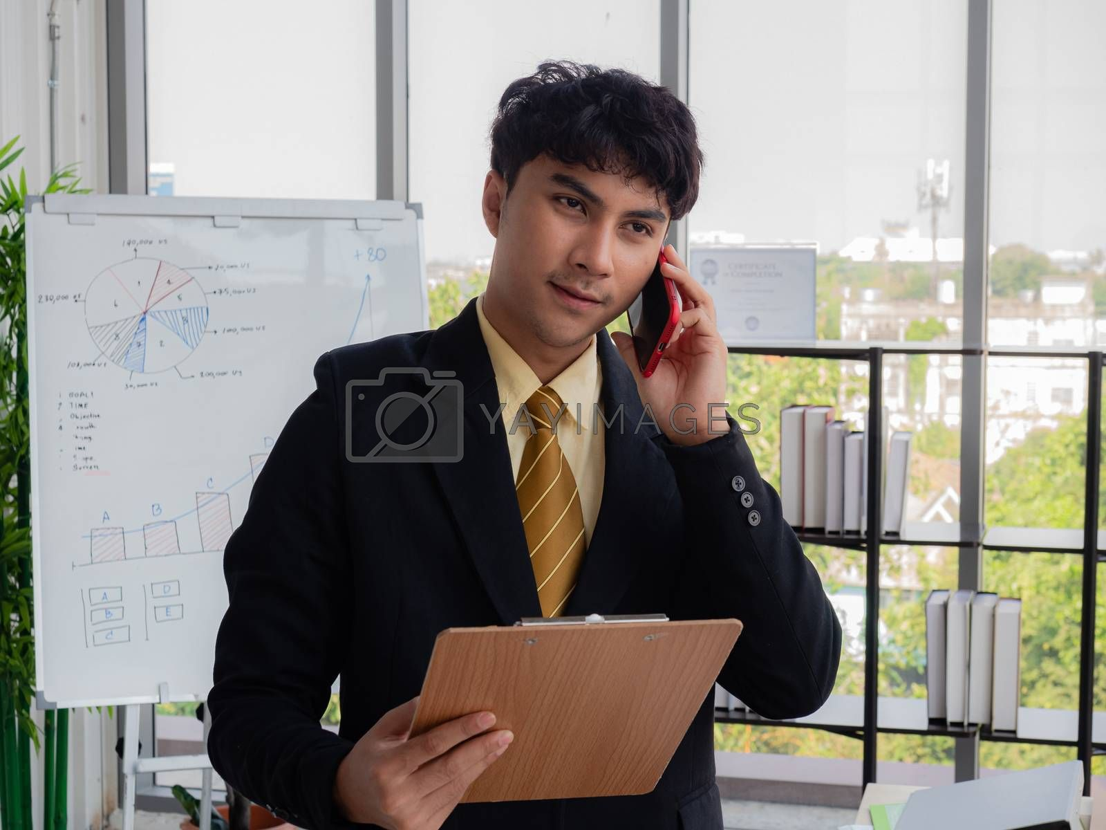 A young Asian businessman is reporting the company's performance to shareholders in a modern office.