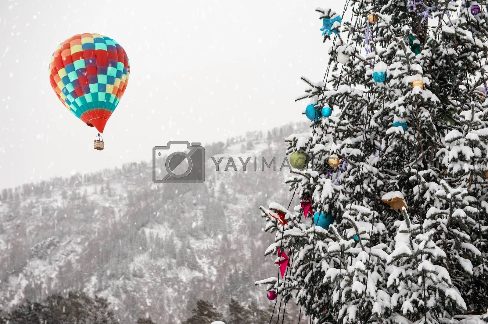 New year fir tree in the mountain forest and aerostat in the sky