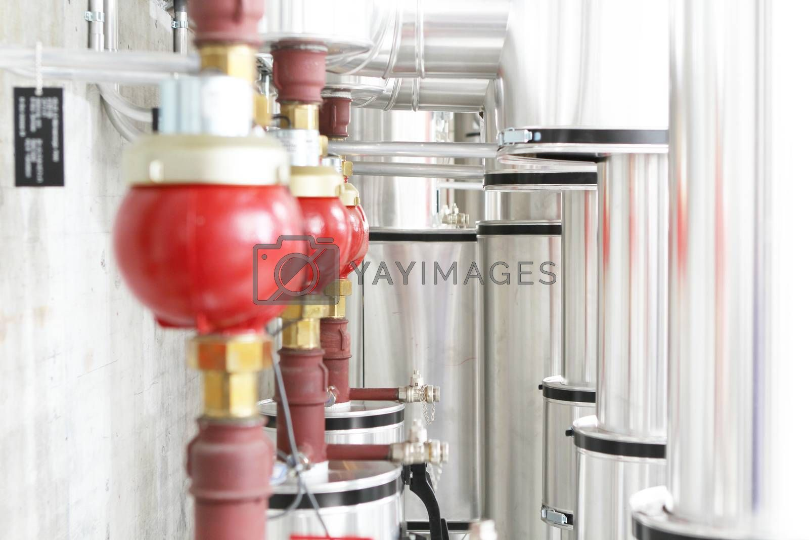 chrome pipes in heating and AC rooms in buildings of factories and hospital. Several pipes with silver pipes and red connector