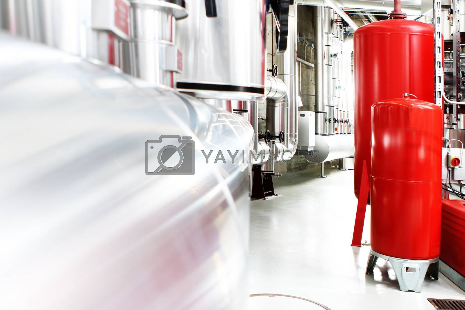 chrome pipes in heating and AC rooms in buildings of factories and hospital. Several pipes with silver and red pipes