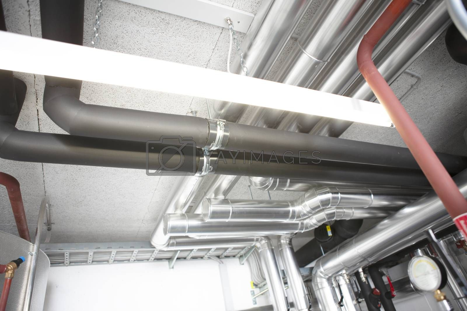 chrome pipes in heating and AC rooms in buildings of factories and hospital shot from below