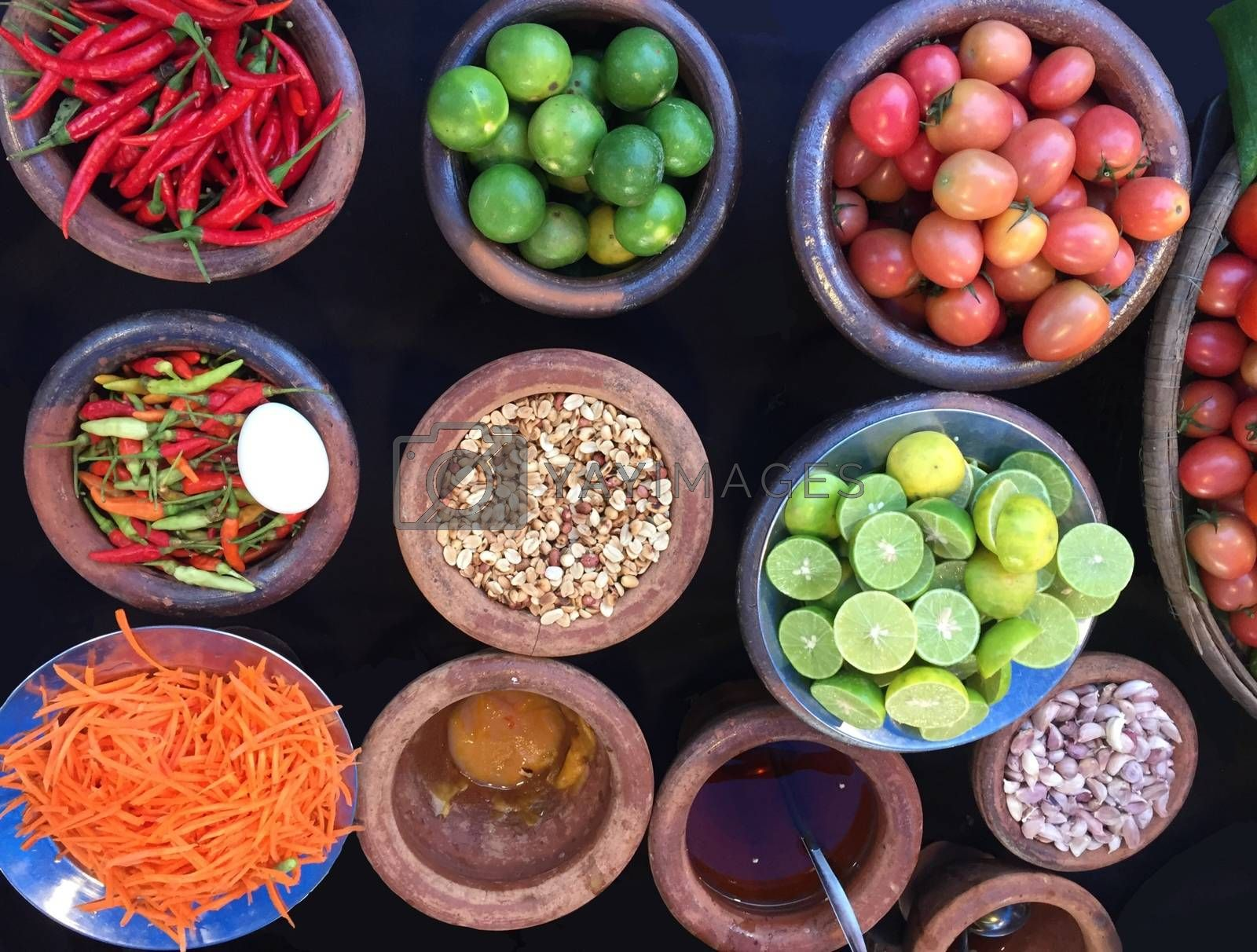 Rustic style raw vegetables, spices in clay or ceramic pots. Top view organic vegetables tomato, hot pepper, carrot, lime in a bowls.