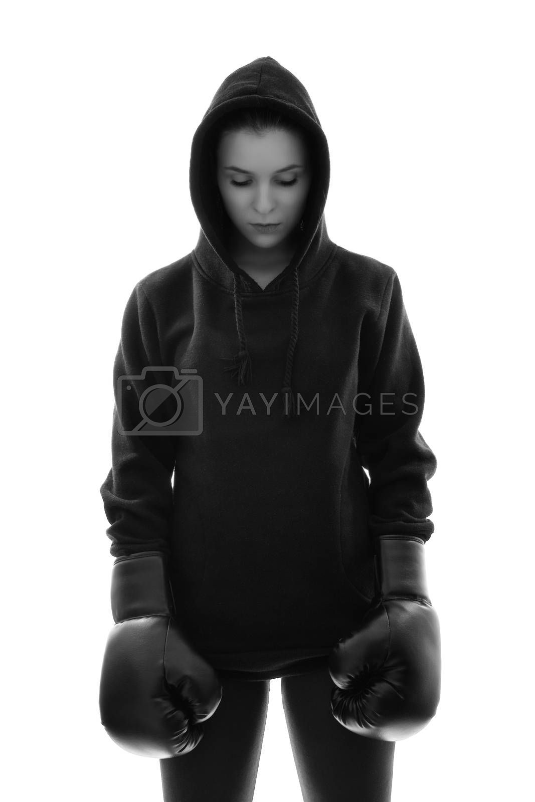 Black and white photo of a focused young beautiful female boxer with hoodie and boxing gloves looking down, backlit silhouette studio shot isolated on white background. Focus, calm, sport concept.