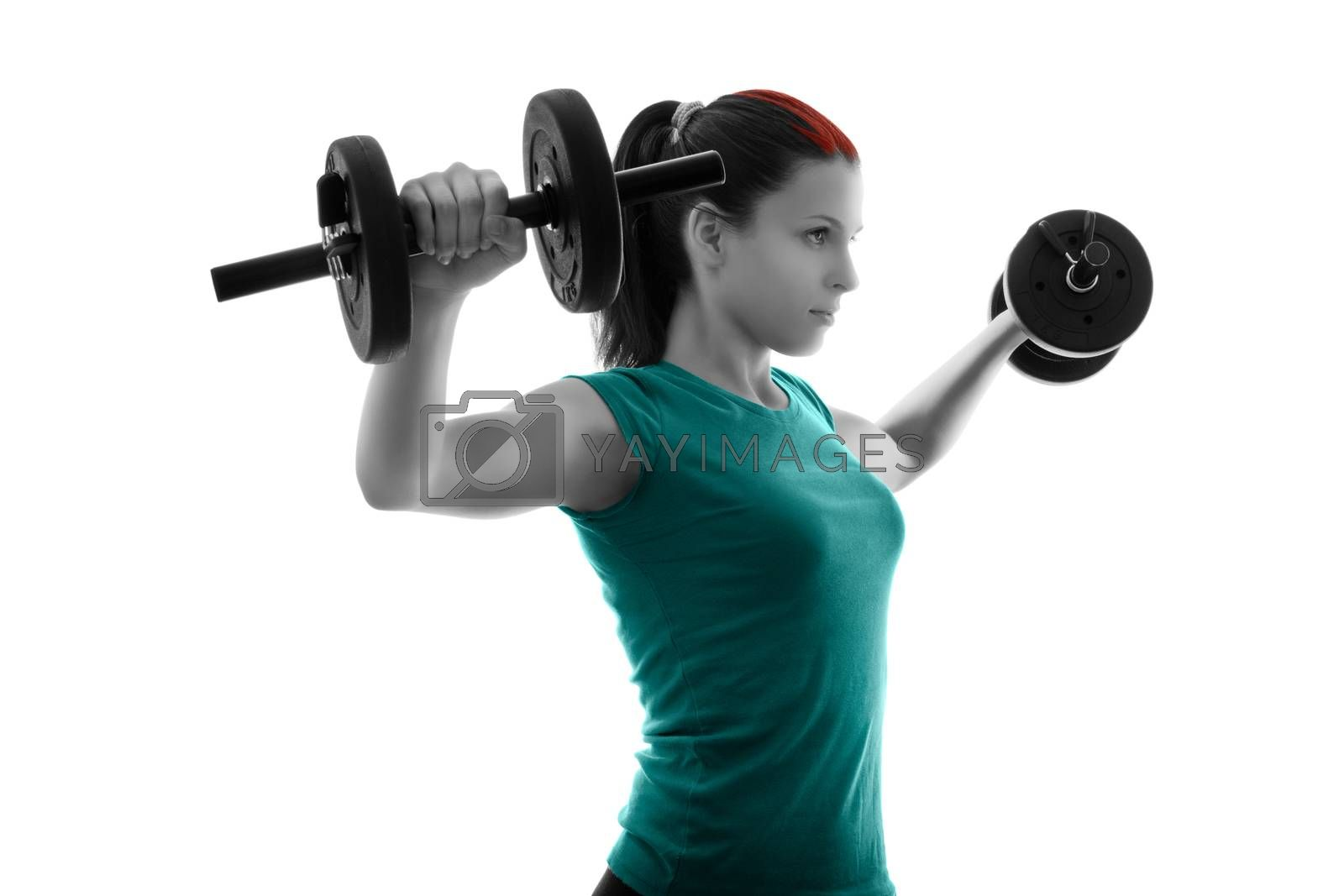 Fit attractive young woman working out with a set of dumbbells, backlit silhouette studio shot isolated on white background. Fitness and healthy lifestyle concept.