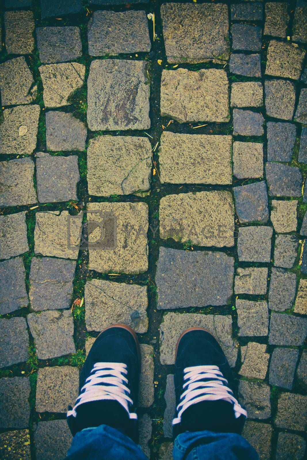 Top down view of feet in a pair of skater sneakers on a cobblestone pavement. Cobblestone patterned background. Minimalist urban style. Feet on cobblestones.