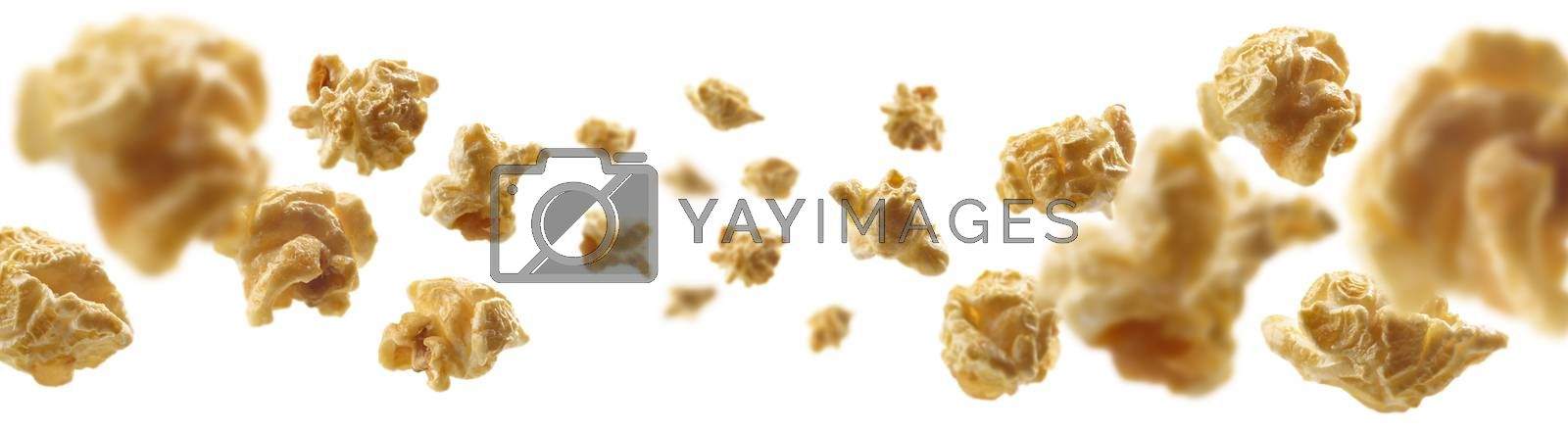 Caramel-flavored popcorn levitates on a white background.