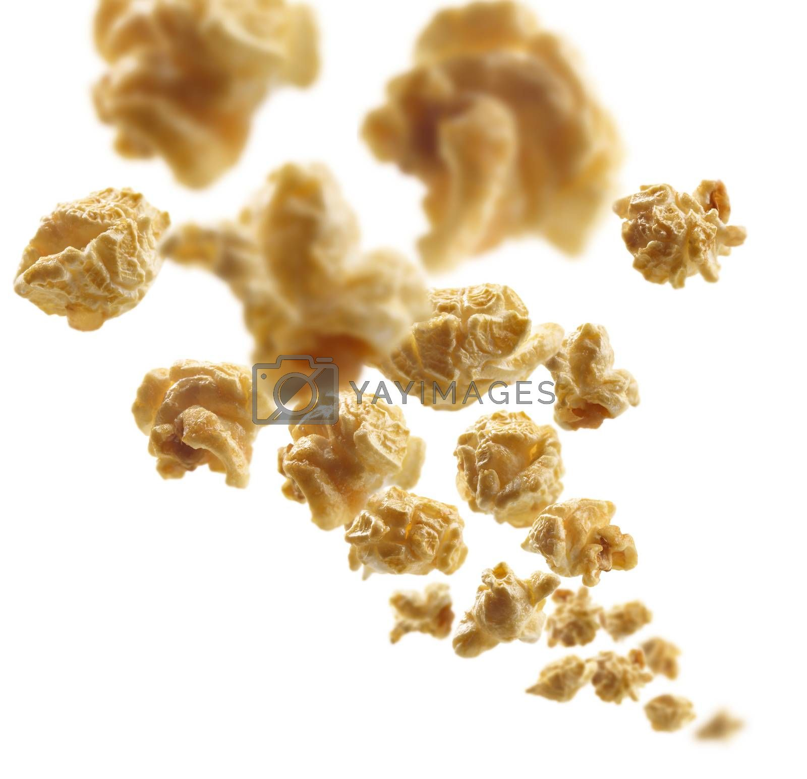 Caramel-flavored popcorn levitates on a white background.