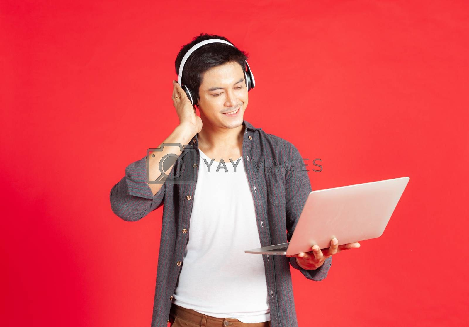 The smart young man is enjoying the music he created from a notebook computer via Bluetooth headphones.