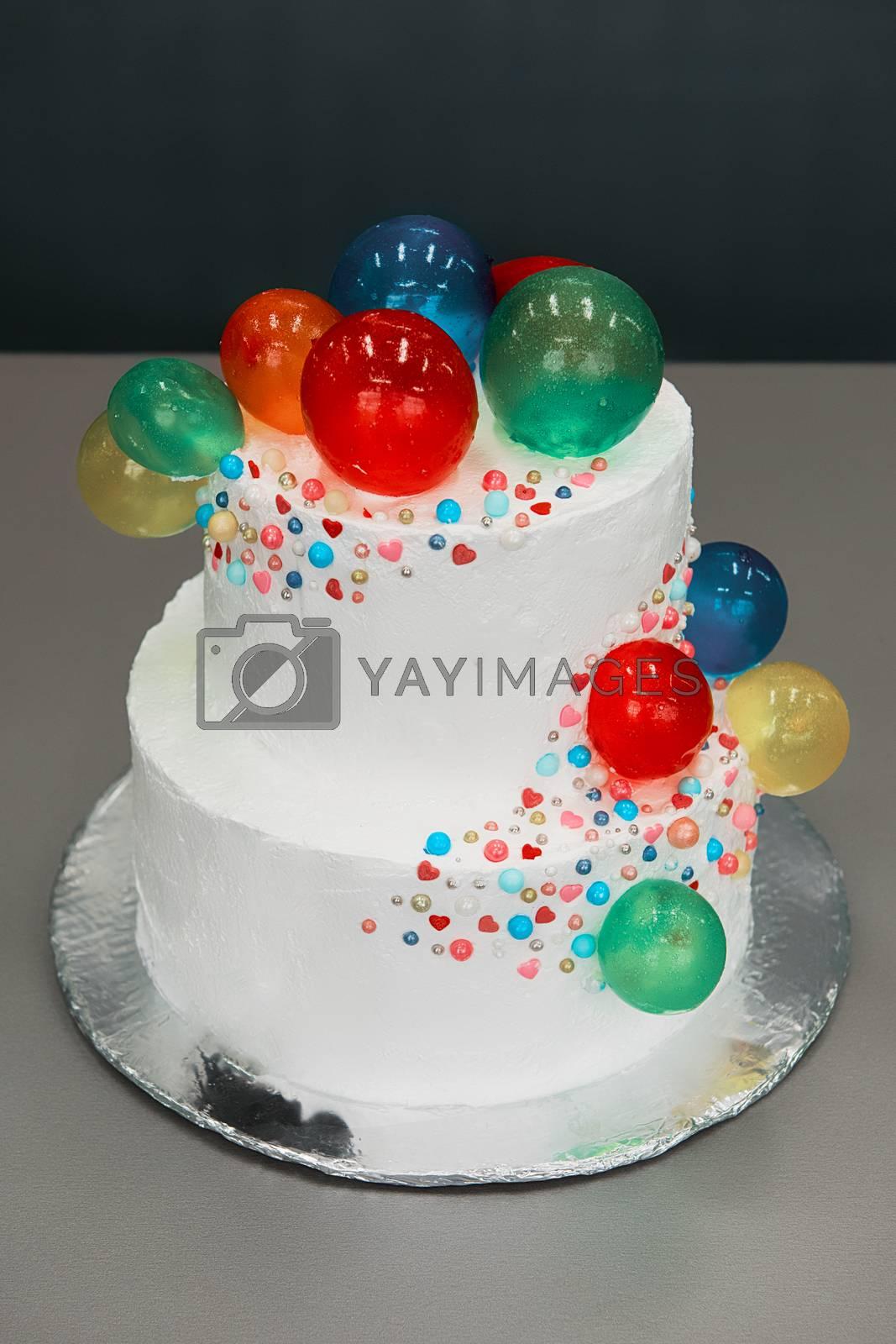 Wedding cake with balloons on grey background