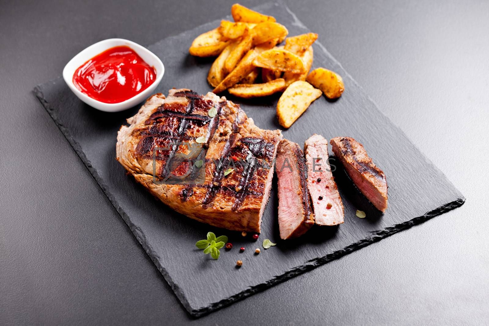 Slate platter of grilled steak with potatoes